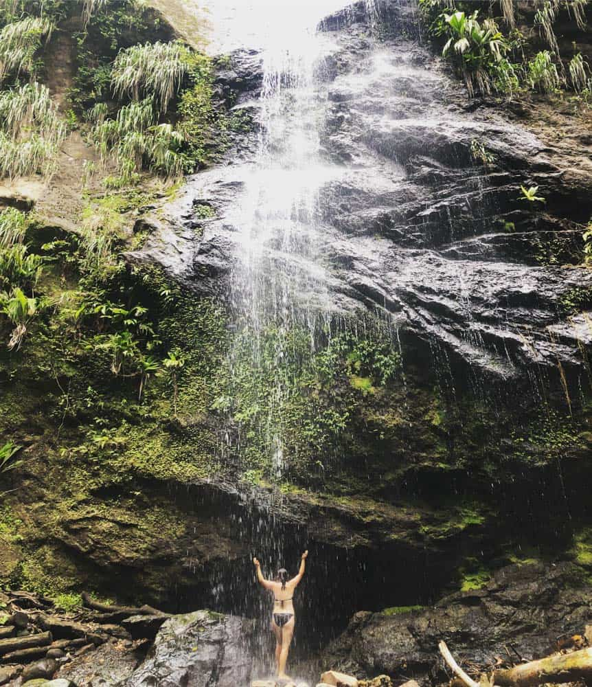 Erin in a bikini standing under a huge waterfall, enjoy a wild shower.