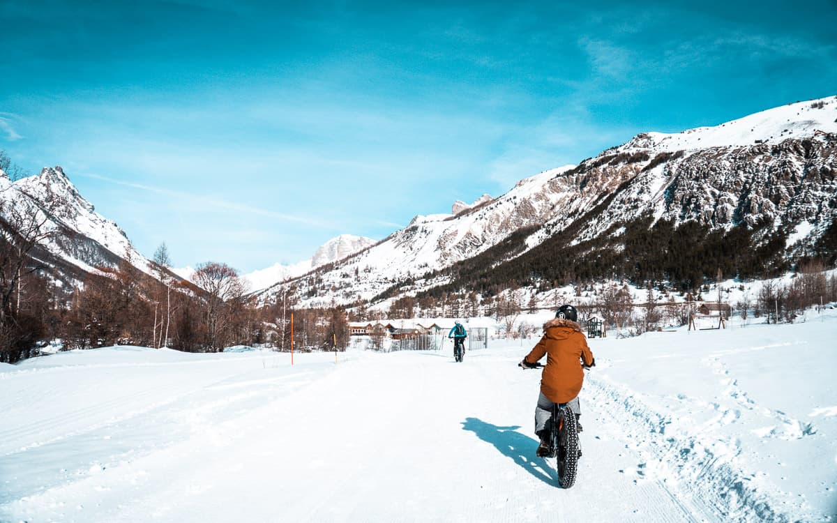 grace fat biking through Ecrins National Park in Serre Chevalier. There's snow on the ground, mountains in the background, and a bright blue sky overhead.