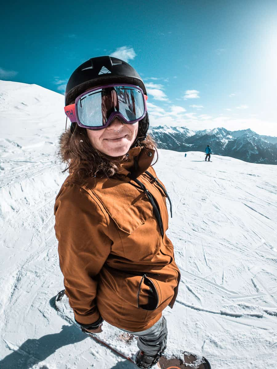 Grace wearing her women's snowboarding gear and smiling on the snowy slopes of Serre Chevalier, France