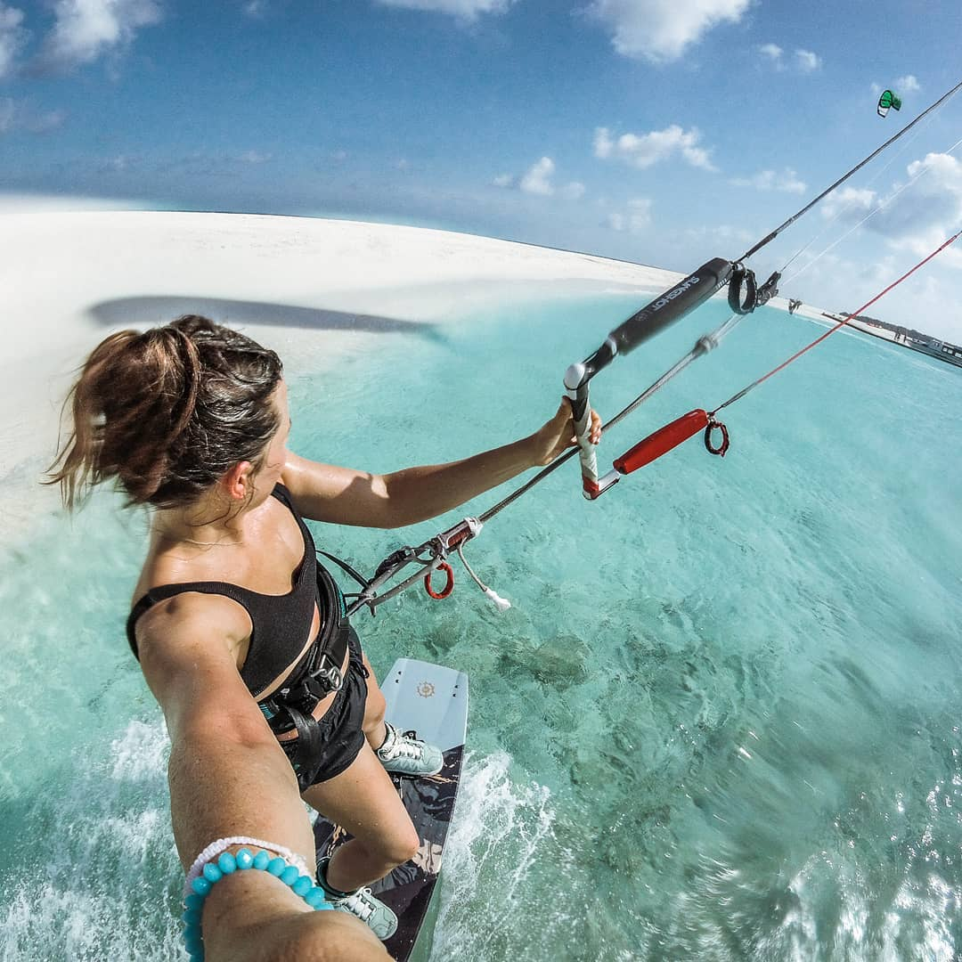 selfie of karolina kitesurfing in the maldives. the water is clear blue, she's near a white sandbar and it looks like a tropical paradise.
