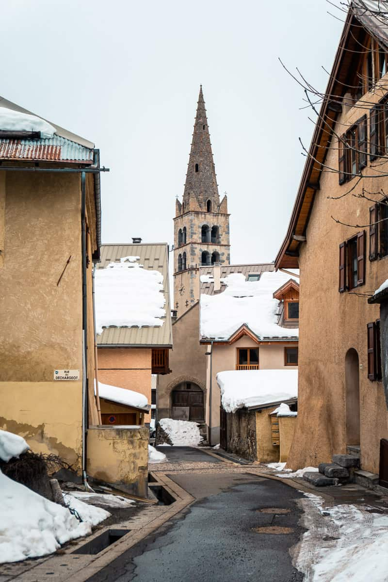 the winding alleys and old architecture of le monetier-les-bains. the village church sits in the moddle of the snowed over road.