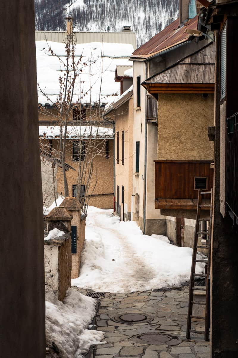 the winding alleys and old architecture of le monetier-les-bains. a ladder is leaning against a platform on the edge of a house. snow covers the ground and rooftops.