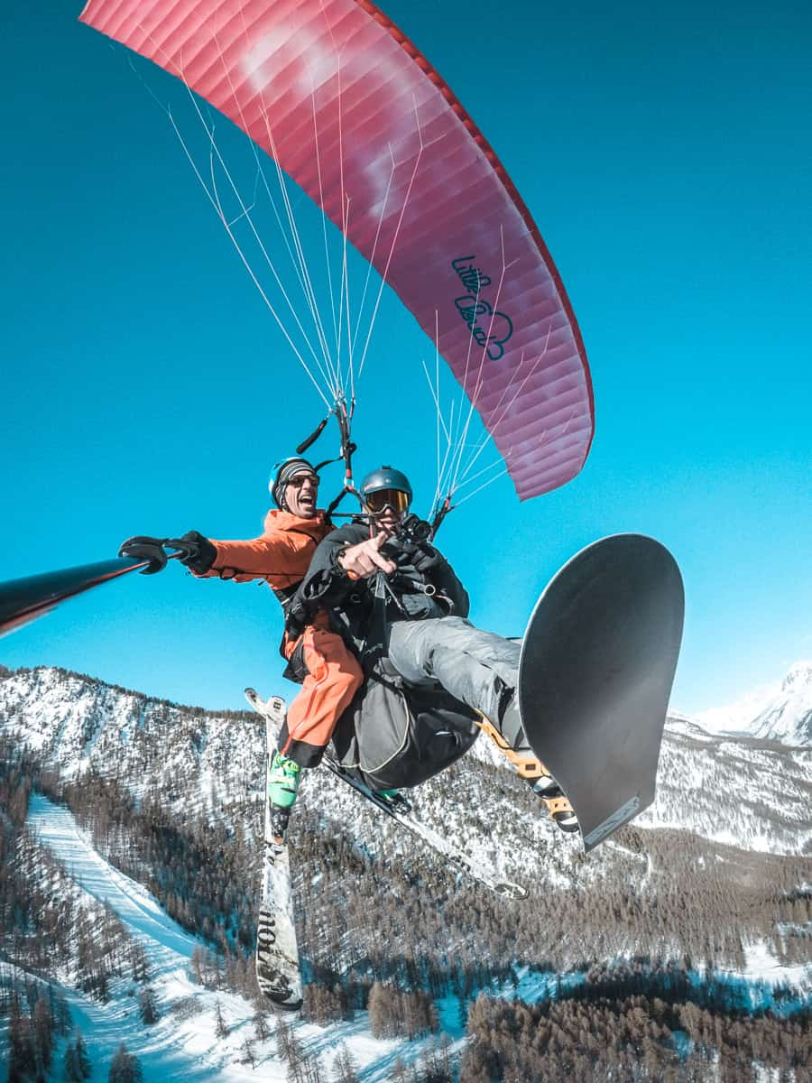 Jim flying with Antoine from Axesse Parapente. They're paragliding over the serre chevaliermountains in winter time on a blue sky day.