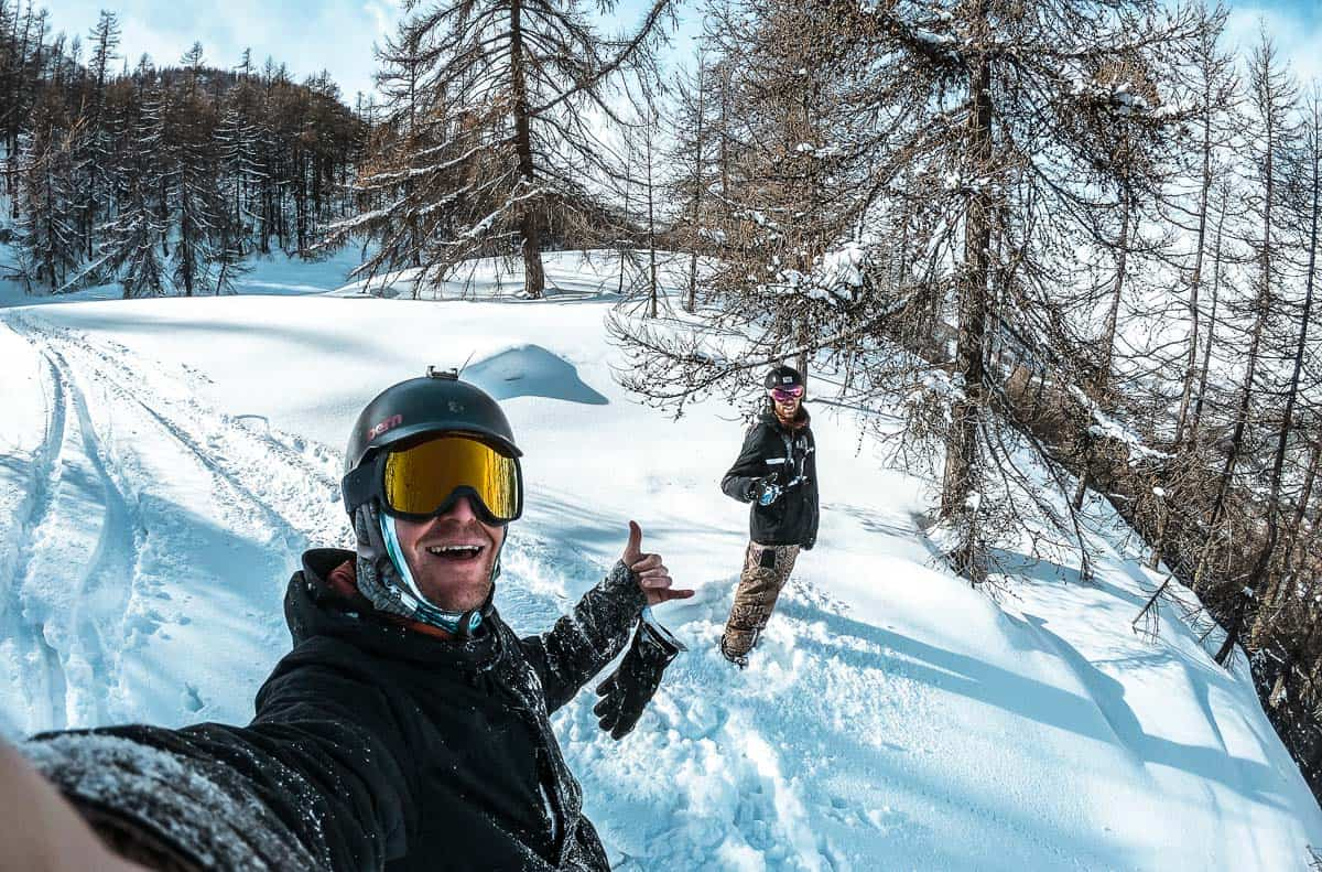 jim and loey are standing in fresh powder on a tree filled slope in serre chevalier. they're wearing their snowboarding gear. jim is smiling and doing a hangloose sign.