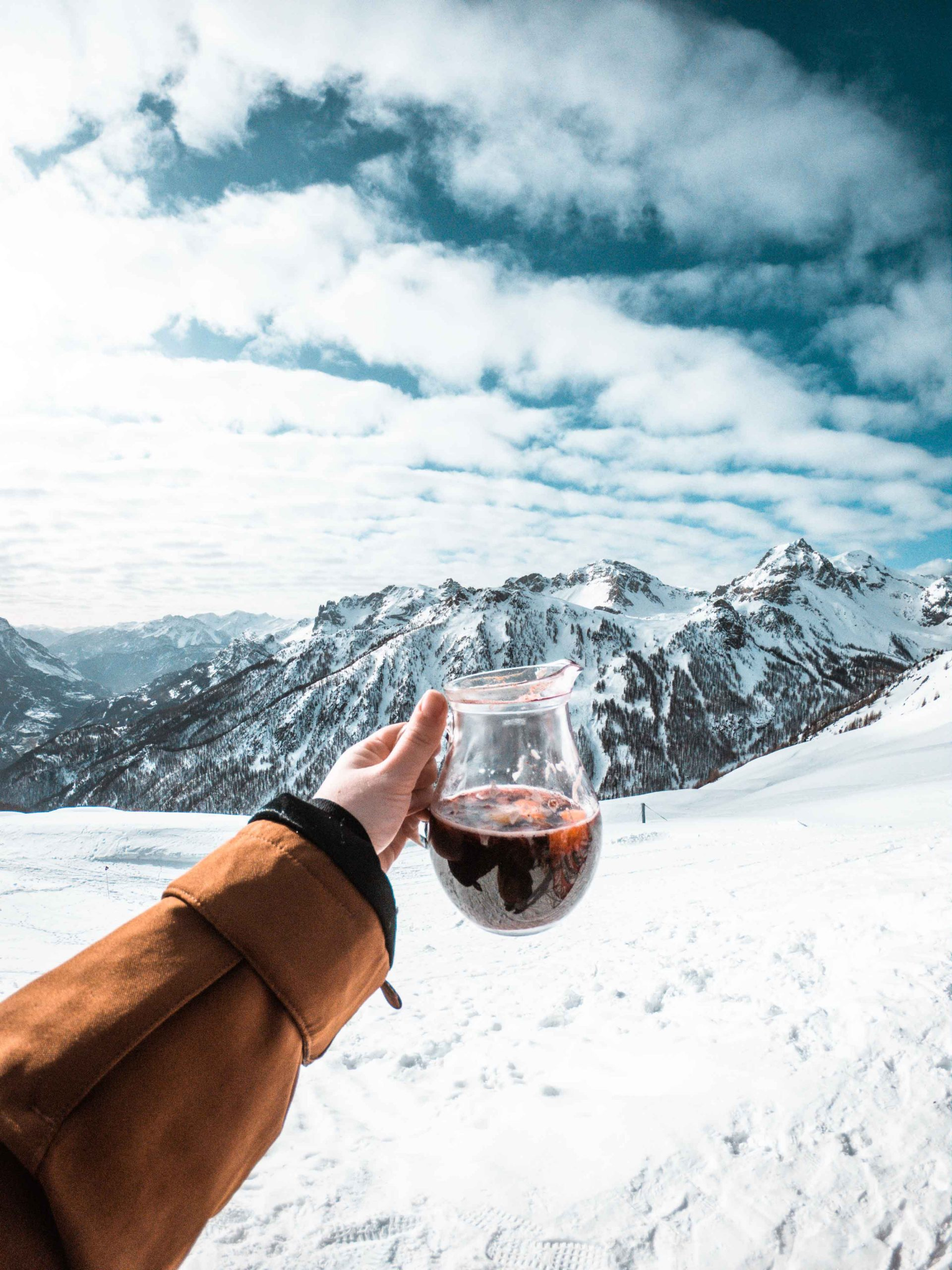 Grace's hand holding a jug of mulled wine against a backdrop of the serre chevalier mountains.