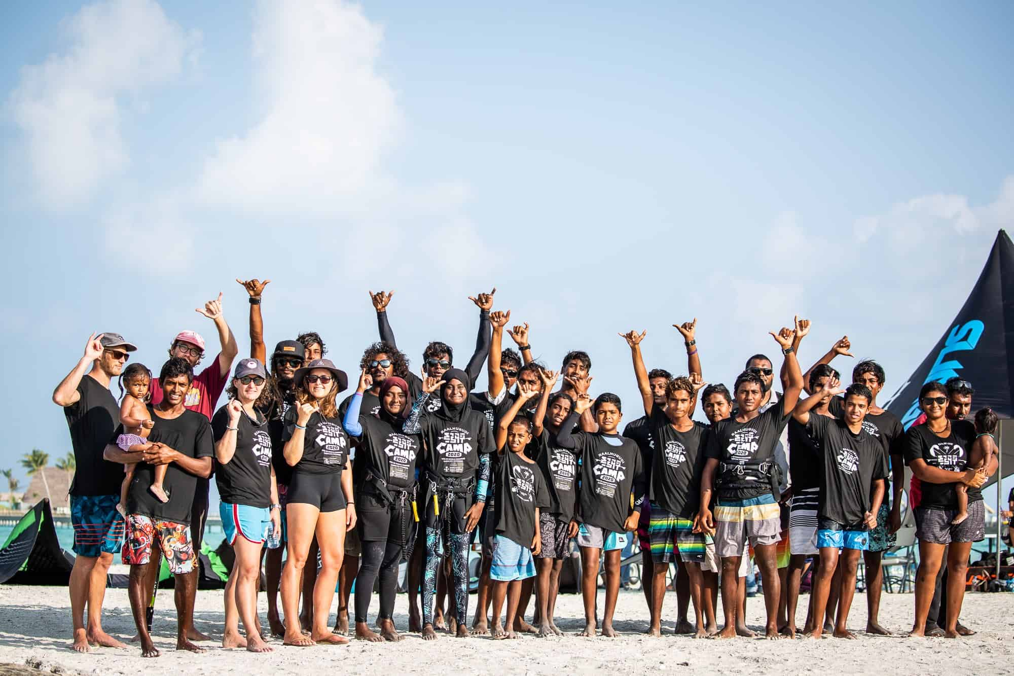 around two dozen people standing together on a sandbar smiling and pulling hang loose signs with their hands. It's the local Maldivian crowd that karolina was teaching how to kitesurf in the Maldives.