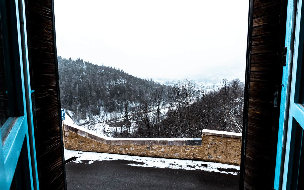 shuttered windows flung open to reveal the snowy landscape of briancon, serre chevalier.