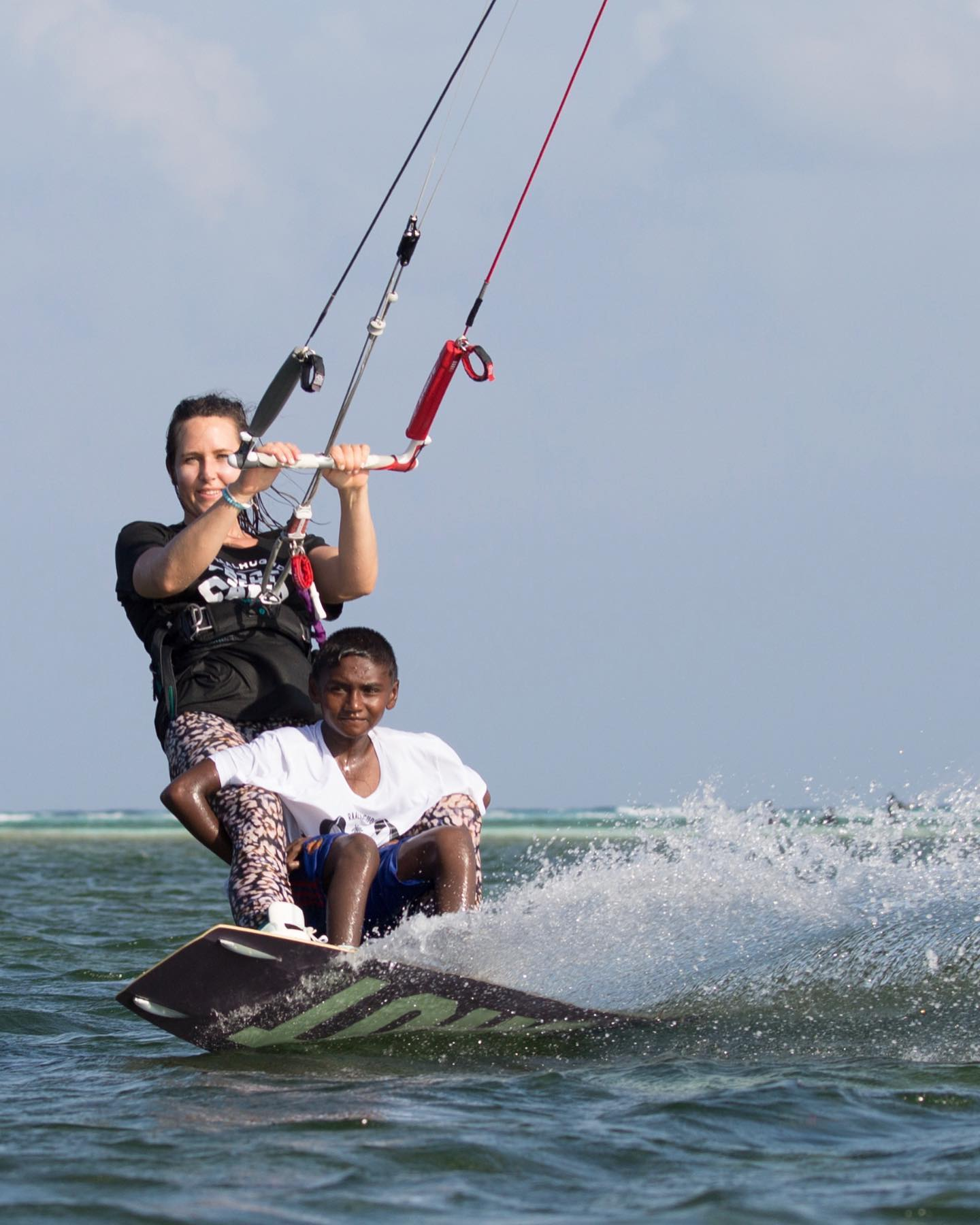 karolina riding her kite with a young Maldivian kid standing on the board holding her legs. They're both smiling and looking relaxed.