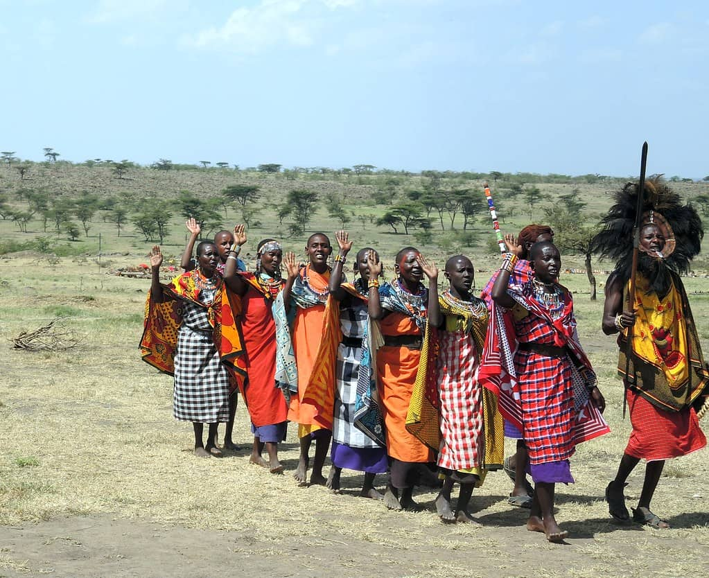 masai mara people wearing colourful robes and standing on parched dusty ground.