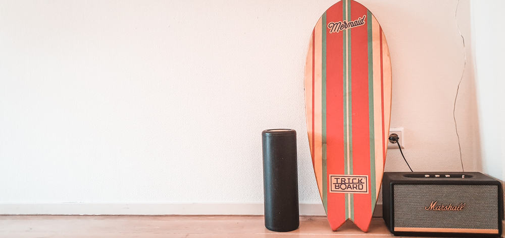 Matteo's indoboard (or balance board, wobble board, etc) leaning against a white wall next to a marshall speaker and a small black case.