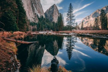 Uomo accovacciato sul bordo di un lago nel Parco Nazionale di Yosemite. Lo scenario drammatico presenta picchi di montagna, pini, sentieri escursionistici e un riflesso soleggiato sull'acqua del lago.
