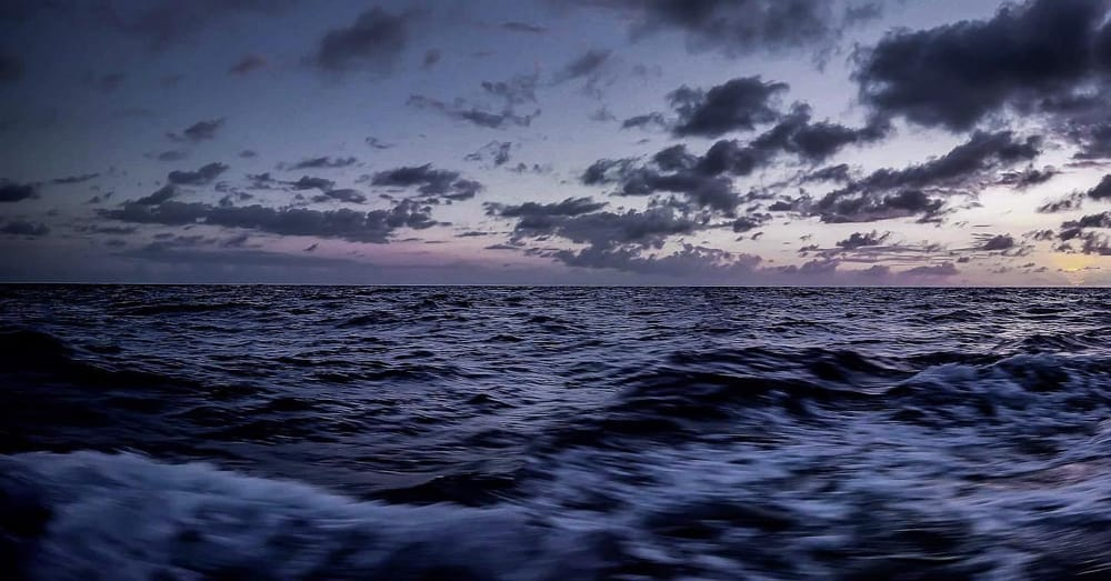 The choppy surface of the ocean at sunset. The sky and the water are a deep purple colour, and the sky is filled with wispy clouds.
