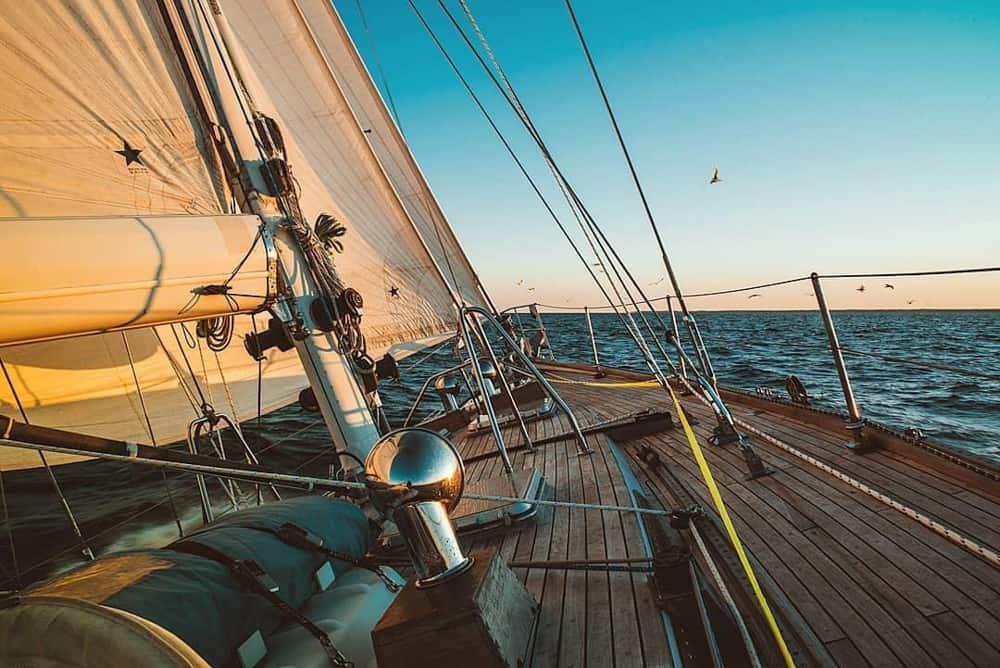 Tiré depuis le pont en bois d'un grand yacht. La voile est levée et les mouettes survolent la surface de l'eau juste au-delà du bateau.