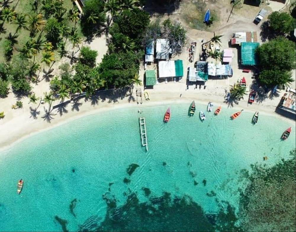 aerial shot of a tropical shoreline. There are some beach huts on the sand and a few colourful fishing boats moored just off the beach. There is a grove of palm trees on the left. The water is crystal clear and aqua coloured.