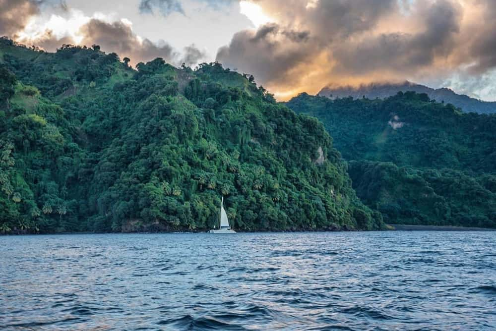 Een wit jacht met opgestoken zeil, aangemeerd voor de kust van een tropisch, verlaten gebied. De lucht is stemmig, het lijkt wel tijd voor zonsondergang. Het water op de voorgrond draagt een lichte chop.