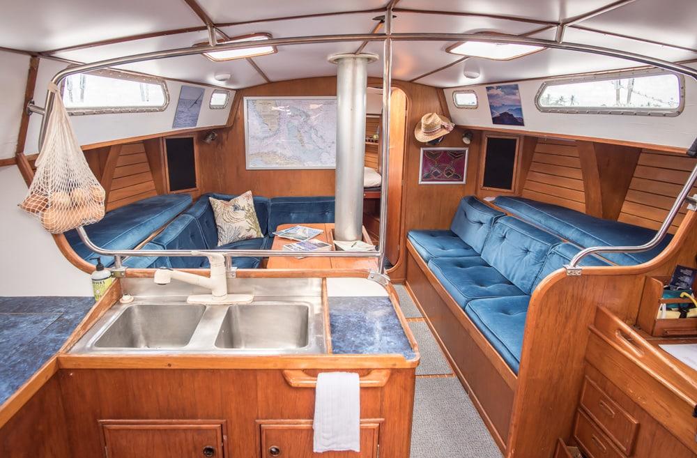 l'intérieur du bateau de Nathan et Vivian, Ultima. Il y a un évier en aluminium au premier plan à gauche, des canapés enveloppants en velours bleu au milieu de la photo, et la porte partiellement ouverte de ce qui semble être la chambre à coucher en arrière-plan.