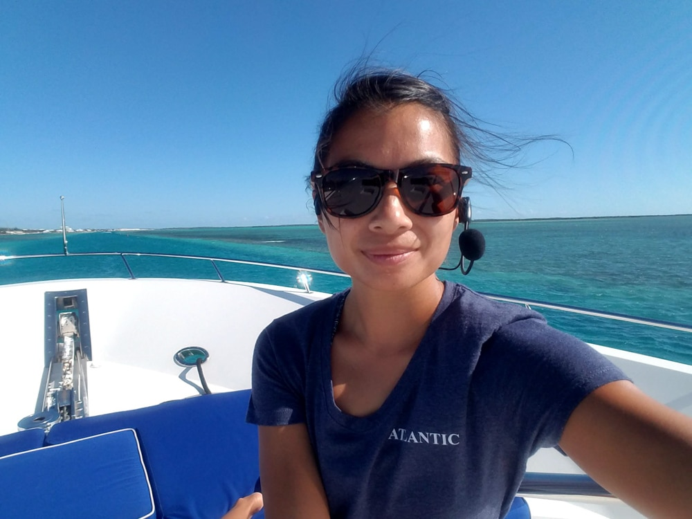 photo of Vivian sitting on the deck of her sailboat. She's wearing sunglasses and a dark blue t-shirt, smiling at the camera. The sky is blue and the aqua water looks warm and tropical.