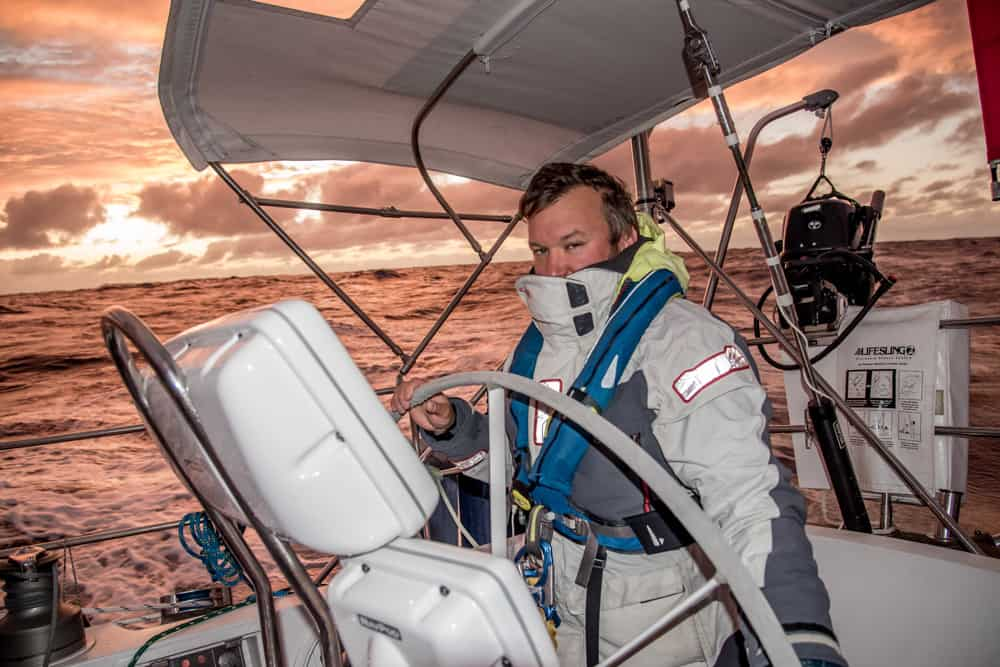Nathan of Ocean passages suited up and on watch at the wheel of their boat. The sky and water behind him are lit up with a peachy pink sunset hue.