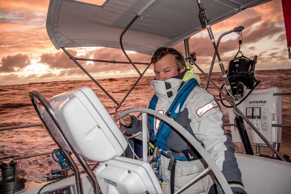 Nathan of Ocean passages s'est habillé et a assuré le quart à la barre de son bateau. Le ciel et l'eau derrière lui sont illuminés d'une teinte rose pêche au coucher du soleil.