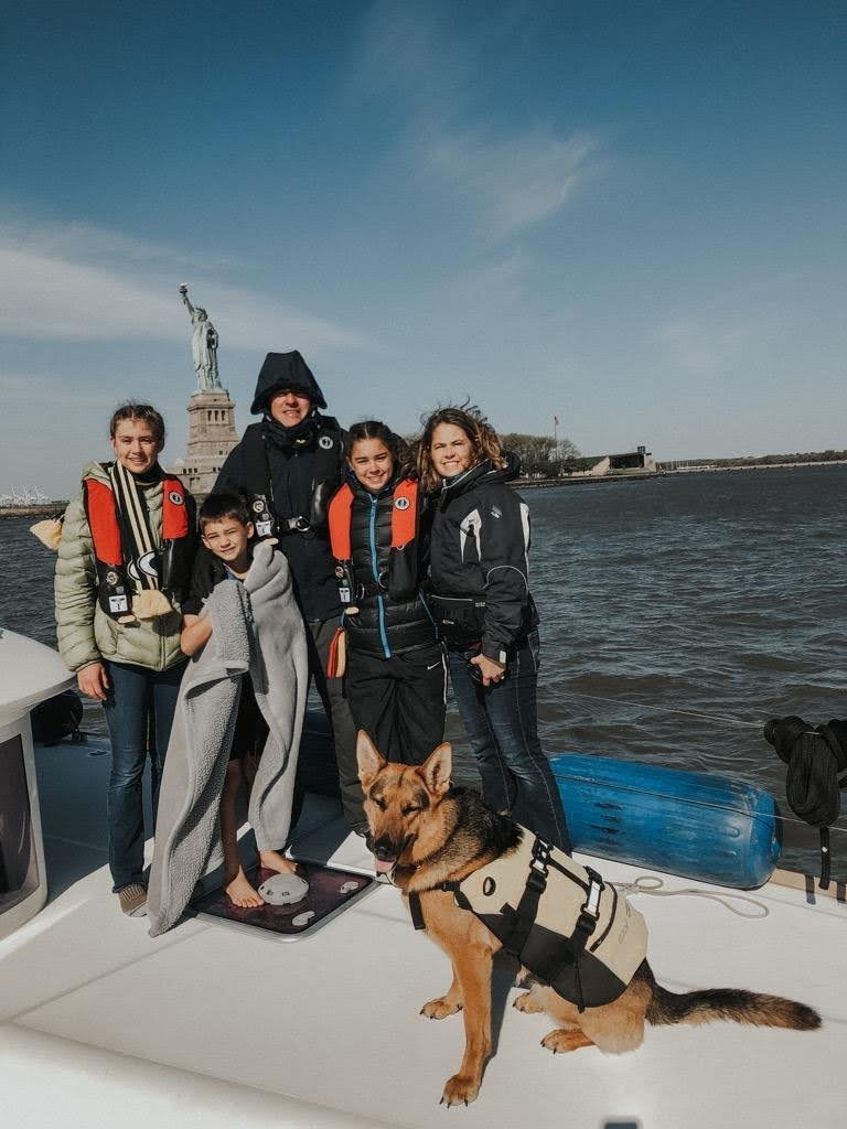 Rosa Linda and her family, along with their german shepard Nala, standing aboard their boat in front of the Statue of Liberty