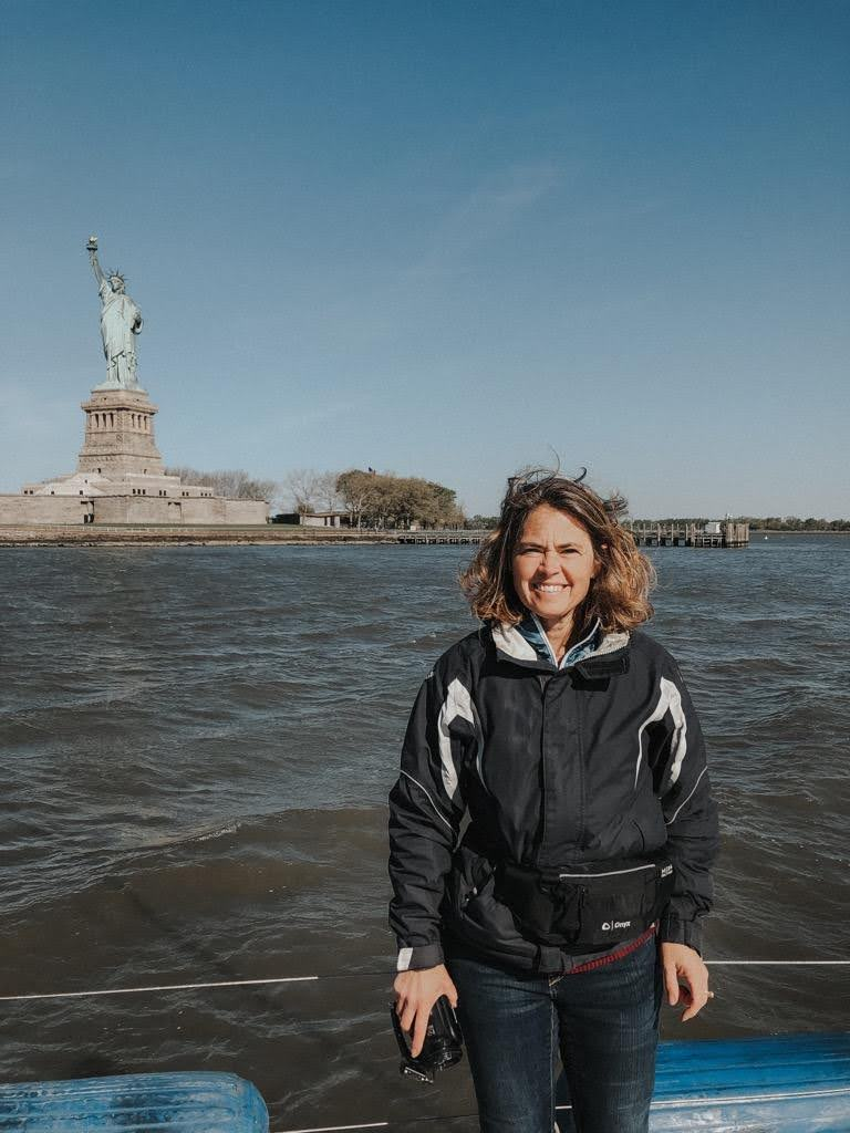 Rosa Linda smiling aboard her boat which is moored in front of the Statue of Liberty