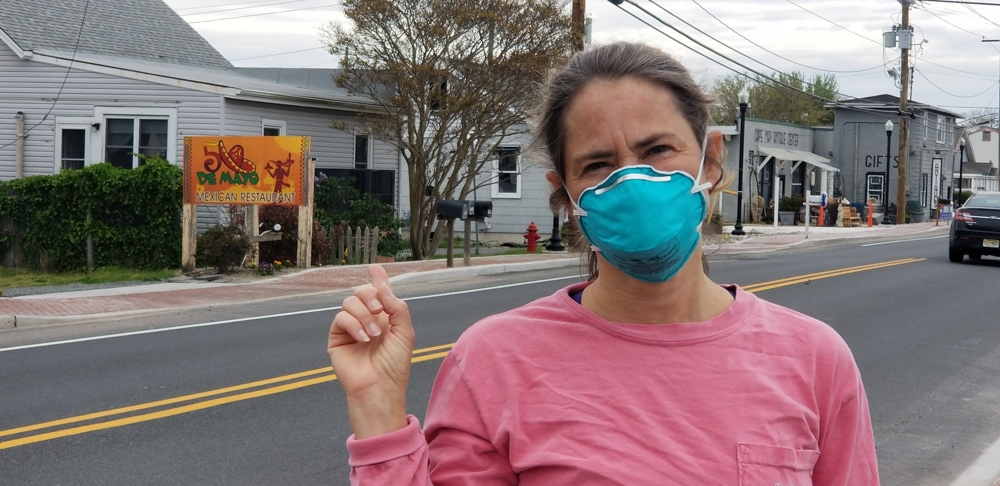 Rosa Linda wearing a pink tshirt and blue N95 face mask. She's standing on a road pointing at a Cinqo de Mayo sign behind her.
